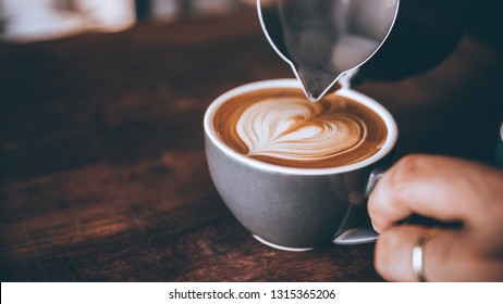 Barista making pouring stream milk with coffee latte art pattern heart shape.