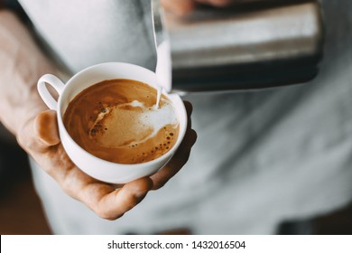 Barista making tasty appetizing coffee cappuccino latte pouring milk. Coffee preparation concept. Closeup