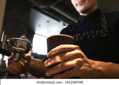 barista man in apron holding hot coffee drink in paper cup in one hand and holder in another. standing close to professional coffee machine in cafe close up