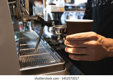 barista man holding hot coffee drink in paper cup in one hand and coffee holder in another standing near professional coffee machine in cafe close up