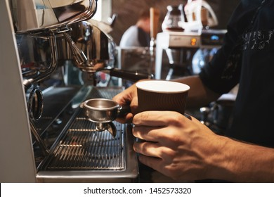barista man holding hot coffee drink in paper cup in one hand and coffee holder in another standing near professional coffee machine in close up