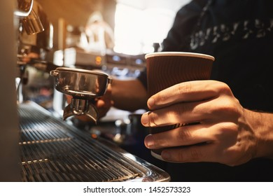 barista man holding hot coffee drink in paper cup in one hand and coffee holder in another standing close to professional coffee machine in cafe close up