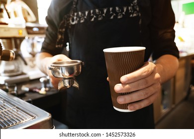 barista man holding hot coffee drink in paper cup in one hand and coffee holder in another standing close to professional coffee machine in cafe