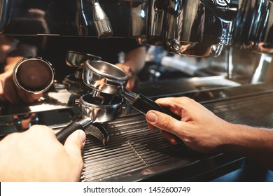 barista man holding two coffee holders one above the other on coffee machine background close up
