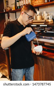 Barista man makes cappuccino in the bar.