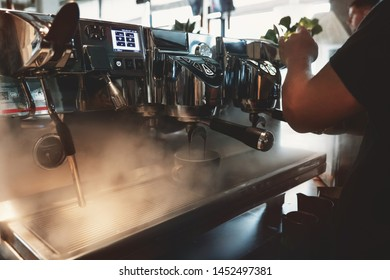 barista man making coffee drink using professional coffee machine steaming around in cafe