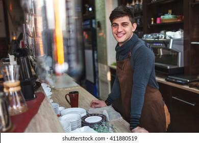 barista man portrait behind the bar in cafe
