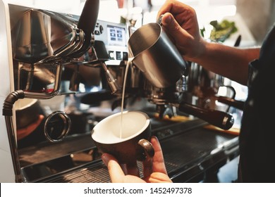 barista man pouring whipped milk from frothing pitcher in cup with coffee standing near professional coffee machine in cafe