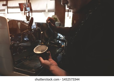 barista man pouring whipped milk from frothing pitcher in cup with coffee drink standing near professional coffee machine in cafe