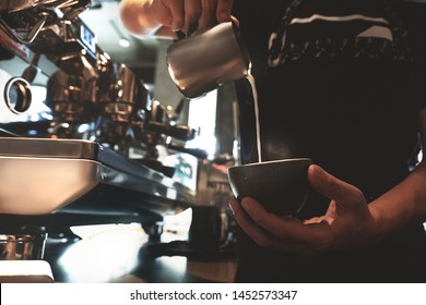 barista man pouring whipped milk from frothing pitcher in cup with coffee standing in front of professional coffee machine in cafe
