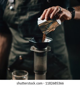 Barista pouring coffee into air press coffee maker.