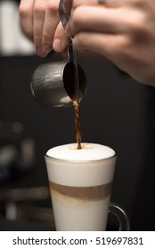 Barista is pouring coffee in milk - preparing coffe latte