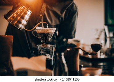 Barista pouring drip coffee into glass. selected focus