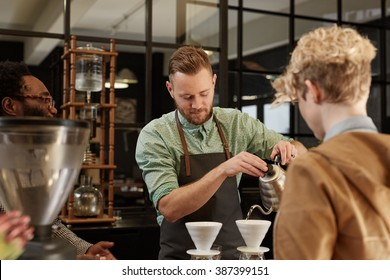 Barista pouring fresh coffee through filter in modern cafe
