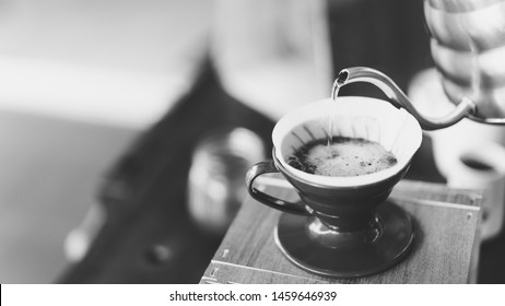 barista pouring hot water on coffee ground, home brewing process, black and whit tone