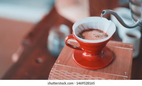 barista pouring hot water on coffee ground, home brewing process, teal and orange tone