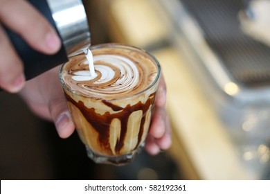 Barista is pouring latte art coffee