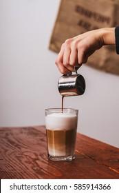 Barista pouring milk in capuccino coffee in coffeeshop