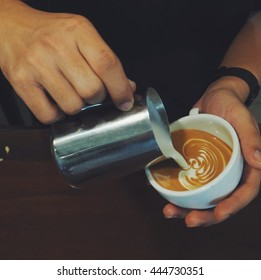 Barista pouring milk in a coffee cup in coffeeshop