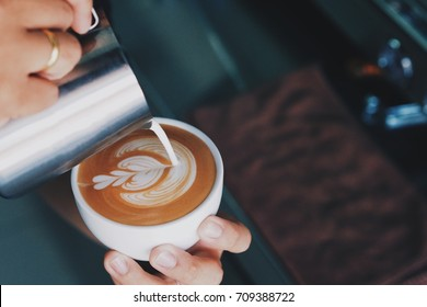 Barista pouring milk in coffee cup for making Coffee latte art.