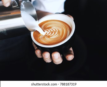 Barista pouring milk in coffee cup for make latte art.