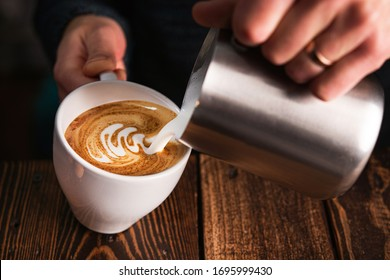 Barista pouring milk into cappuccino cup. Latte art background.