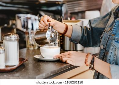 Barista pouring milk into coffee at bar counter
