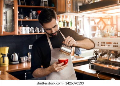 Barista pouring milk into cup of coffee in shop