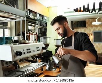 Barista pouring milk into metal pitcher near coffee machine at bar