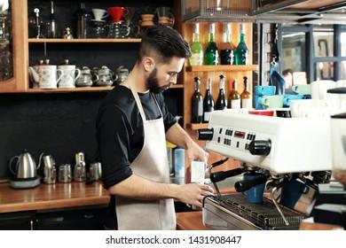 Barista pouring milk into metal jug near coffee machine at bar