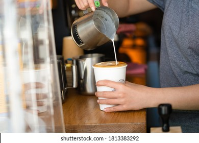 a barista pouring milk making a take away coffee