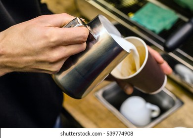 Barista pouring milk to takeaway coffee. Close-up view on hands, small coffee business concept.