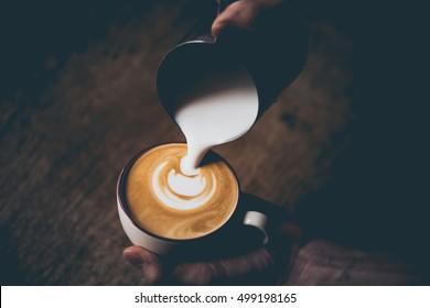 Barista pours milk making cappuccino or latte. Toned picture
