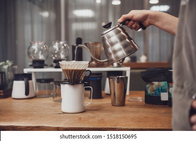 Barista pours over coffee in funnel. Barista's hand hold metal kettle with boiling water