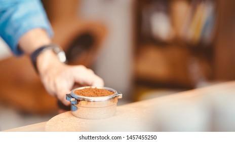 barista prepare coffee ground in group head to brew espresso coffee, teal and orange tone