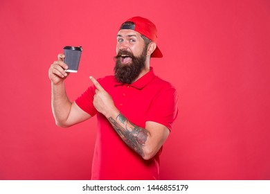 Barista prepared drink for you. Cheerful barista. Man bearded hipster red cap uniform hold paper coffee cup. Barista recommend caffeine beverage. Barista job position. Coffee shop staff wanted.