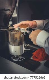 Barista prepares coffee powder for making coffee in his coffee shop, close-up