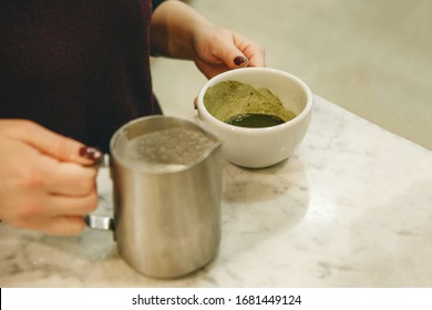 Barista prepares tasty and healthy matcha latte tea.