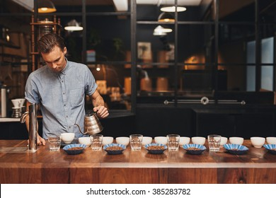 Barista preparing coffee tasting with rows of cups and beans