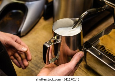 Barista preparing milk for takeaway coffee. Close-up view on hands, barista coffee preparation service concept.