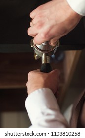 Barista presses ground coffee using tamper.
