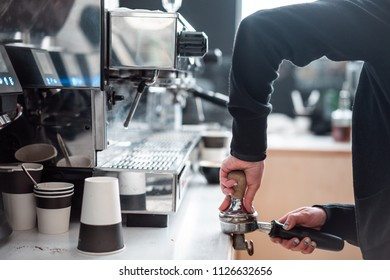Barista presses ground coffee using tamper. Close-up view on hands.