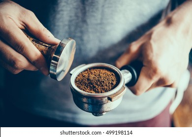 Barista presses ground coffee using tamper. Toned picture