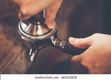 Barista presses ground coffee using tamper. Close-up view on hands with portafilter, small coffee business concept. color vintage style ,Thailand