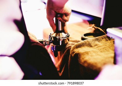 Barista pressing fresh coffee grinds at the coffee shop