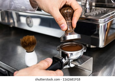Barista pressing ground coffee into portafilter with a tamper.