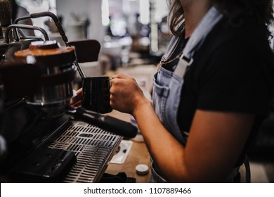 Barista steaming milk on espresso machine, bartender making coffee in coffee shop