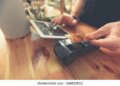 Barista taking credit card to do payment for visitor