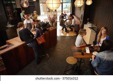 Barista taking an order from friendly customers in a cafe