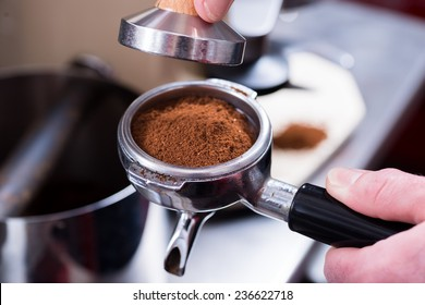 Barista with tamper and piston/portafilter making espresso.